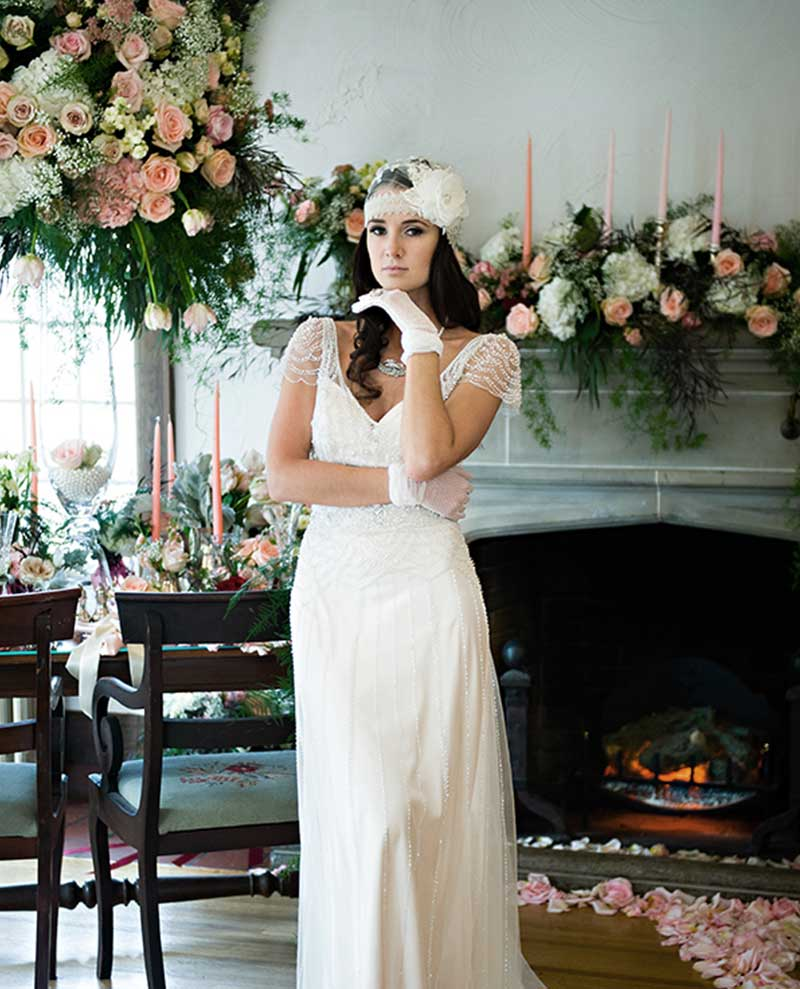 Bride stands in front of elaborate flowers draped over fireplace