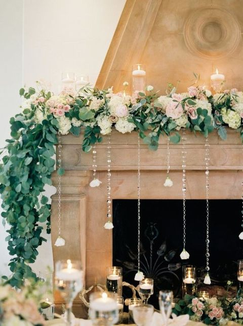 Flowers draped over mantle place with crystal strings dangling from flowers in front of hearth