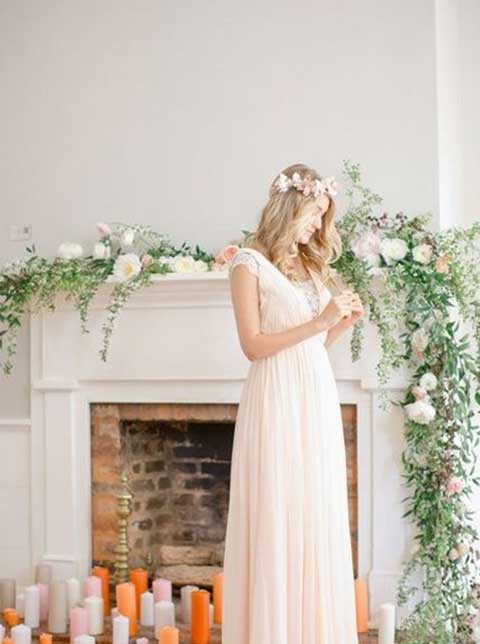Whimsical bride stands in front of greenery-draped fireplace. Candles decorate the floor