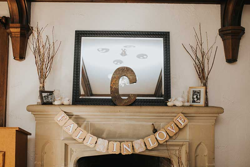 """Fall in Love"" on square paper draped over a fireplace mantle"