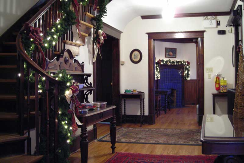 Christmas lights, bows and evergreen boughs decorate staircase and fireplace