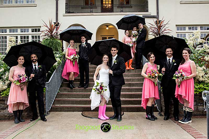 Bridal party poses on steps with rubber boots and umbrellas