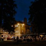 Guests at Elsie Perrin patio photographed from a distance at night